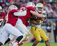 Tarean Folston (25) is tackled by Stanford Cardinal linebacker Kevin Anderson (48) and defensive end Henry Anderson (91) in the first quarter.