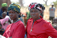 Tansania, Shinyanga, christliche Frauen in roter Bluse und Kruzifix auf Markt im Meatu Distikt / Tanzania, christian women wearing a cross at market in in Meatu district