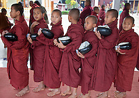 Myanmar, Burma.  Young Buddhist Monks Lined up to Receive Charitable Gifts from Wealthy Donor, Alodaw Pauk Pagoda, Nampan Village, Inle Lake, Shan State.  Each boy holds in his hand a coupon he will present to receive his gift.