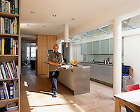 A portrait of home owner Ann Grut in the contemporary kitchen and dining space of her London home.