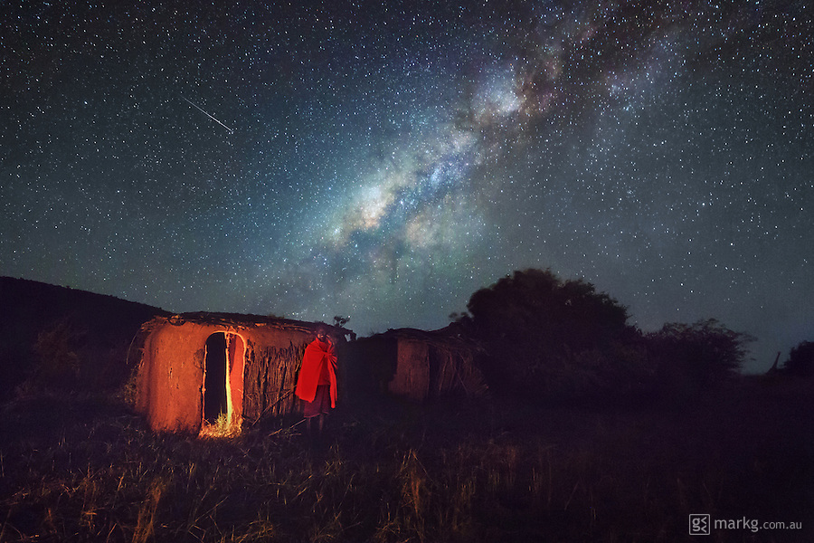 One of the unexpected highlights of my trip to Mara Bushtops in Africa was the people and the culture. I hadn&rsquo;t really thought about it much before I got there, as all I had on my mind was epic night skies and amazing wildlife. But as soon as I touched down in the Mara, I was greeted by the Masai (Maasai) people, and then interacted with them every day during my time there. I was assigned a Masai Warrior for my security and as a spotter, and he even helped me with all my camera equipment that I would bring along for the game drives and photo missions.<br /> <br /> I also got to visit a traditional Masai Enkang and was invited into one of the huts within the Enkang. I was offered cows milk and blood to drink, which I politely declined, but it was incredible to see how the Masai live even today without all of the mod-cons the western world take for granted - in fact the Masai gauge their wealth by the amount of cattle they have, and I was told that if you were to offer them either a Ferrari car or cattle, they would definitely take the cattle. <br /> <br /> In this photo, one of the Masai pose outside a traditional hut under the night sky with the Milky Way over head complete with shooting star! The huts are traditionally constructed by the women and are made with timber poles interwoven with a lattice of smaller branches, and then plastered with a mixture of sticks, grass, cow dung and ash which bakes hard in the hot sun.