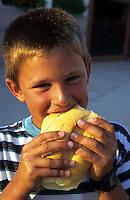 SPAIN, boy eat bread roll / SPANIEN, Junge isst ein Broetchen