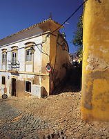Old-style Portuguese houses painted in traditional white and yellow, in a cobbled street in the town of Silves, Algarve, Portuga