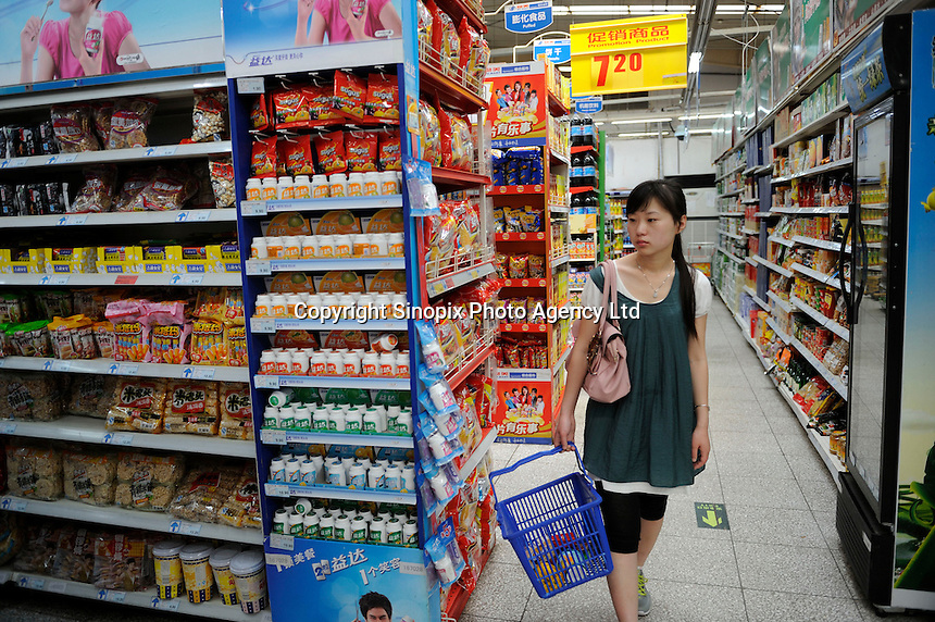 A girl shopping at a Wu Mart supermarket in Beijing, China. Wu Mart, the Beijing-based chain, was founded in the early 1990s by Zhang Wenzhong. Its name smacks of the fame of U.S. retail giant Wal-Mart. Wu Mart and Wal-Mart are competing in different arenas and each appears to be going after a different class of consumer. By 2005, Wu Mart had more than 450 hypermarkets, supermarkets and convenience stores, and is one of only a few Chinese retailers whose shares are publicly traded..28 May 2011