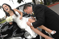 Danielle enjoys her soon to be husband  Ian placing her garter belt on her leg, before their wedding in Manteca, CA