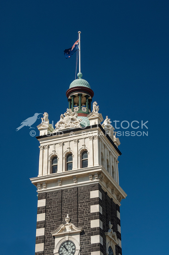 Close up of the clock tower at the Dunedin Railway Station with the New Zealand flag flying, Otago, New Zealand - stock photo, canvas, fine art print