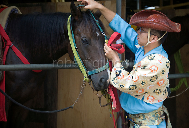 An archer prepares one of the horses that will take part in the annual Reitaisai Grand Festival at Tsurugaoka Hachimangu Shrine in Kamakura, Japan on  14 Sept. 2012.  Sept 14 marks the first day of the 3-day Reitaisai festival, which starts early in the morning when shrine priests and officials perform a purification ritual in the ocean during a rite known as hamaorisai and limaxes with a display of yabusame horseback archery. Photographer: Robert Gilhooly