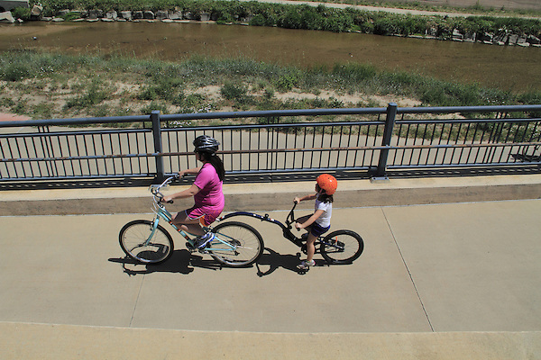 Mother and daughter riding their tandem bike on a sidewalk in Denver, Colorado. .  John offers private photo tours in Denver, Boulder and throughout Colorado. Year-round.