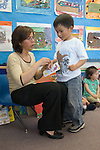 Berkeley CA  Preschool teacher awarding student a star for the day as he prepares to go home.