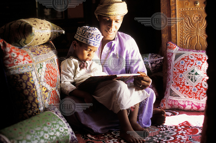 A father reading a book to his son at home.
