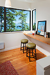 An upstairs office space offers a beautiful view of the water and mountains in this island home. This image is available through an alternate architectural stock image agency, Collinstock located here: http://www.collinstock.com
