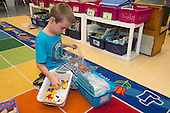 MR / Schenectady, NY. Zoller Elementary School (urban public school). Kindergarten classroom. Boy (5) with hearing aid puts away learning materials after learning center time. MR: Sch20. ID: AM-gKw. © Ellen B. Senisi.