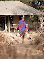 Maasai tribesman cleaning tents at Eco Tourist Campsite. Near Amboseli National Park, Rift Valley Province, Kenya