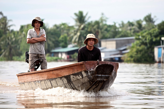 Two men in a boat speed down the Hau River in the Mekong Delta, south of Can Tho, Vietnam. Sept. 30, 2011.