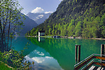 Boat house, marina and reflections of mountain and trees, Lake Plansee near Reutte, Austrian Alps.