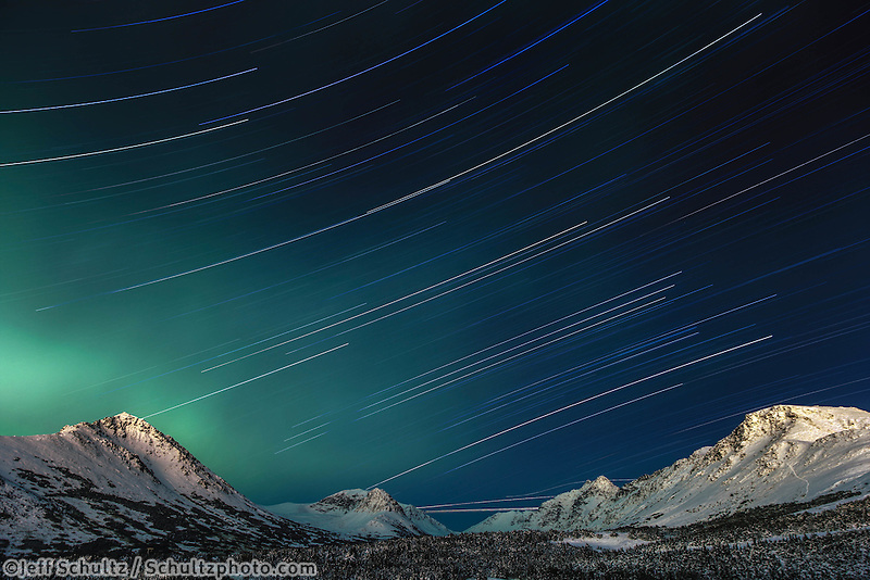 Winter landscape of star trails and Northern Lights (aurora) over several peaks of the Chugach Mountains in Anchorage, Alaska.  Peaks include; O'Malley, The Wedge, Suicide Peak, Flattop mountain