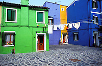 Italy, Island of Burano. Colorful fishermans homes with laundry hanging. One of the islands near Venice