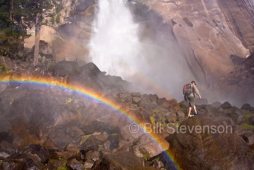 A man hiking beneath Nevada Falls and a rainbow in the springtime in Yosemite National Park in California