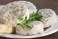 French goat cheese - chevre - with herbs on a white plate on a wooden table. Young (not aged) fresh type Clos des Iles Le Brusc Six Fours Cote d'Azur Var France