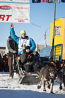 Travis Beals and team leave the ceremonial start line at 4th Avenue and D street in downtown Anchorage during the 2014 Iditarod race.<br /> Photo by Jim R. Kohl/IditarodPhotos.com