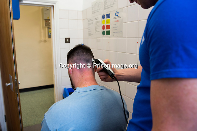 A prisoner cutting the hair of another prisoner with a trimmer on the enhanced wing of HMP Swansea, Wales. (Photo credit MUST read: © Prisonimage.org)