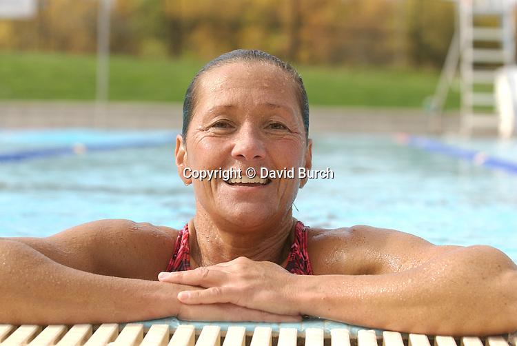 Smilin woman on edge of swimming pool