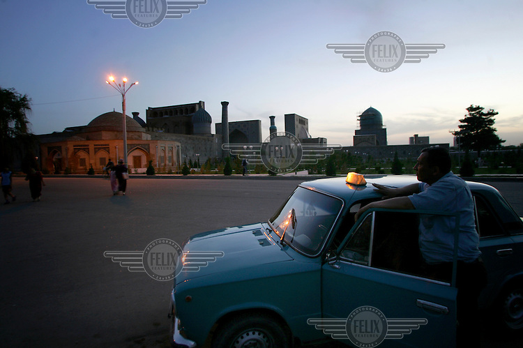 A taxi driver waits for customers near the Registan.