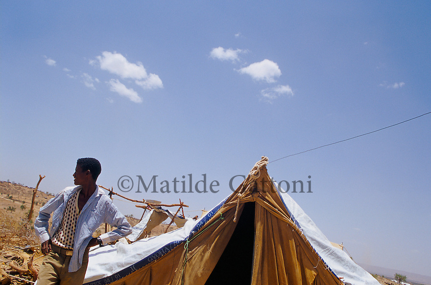 Eritrea - Debub- Young boy standing next to his family tent in an IDP camp. As a result of 30 years of war for independence against Ethiopia (from 1961 to 1991) and another 3 years from 1997 to 2000, there are 50,000 Eritreans currently living in internally displaced (IDP) camps throughout the country. These IDPs have fled three times in the last 10 years, each time because of renewed military conflict. They lived in relatives' homes when lucky enough, but mostly, the fled to the mountains, where they attempted to do what Eritreans do best, survive. Currently there is no Ethiopian occupation in Eritrea, but landmines prevent the IDPs from finally going home. .It is estimated that every Eritrean family lost two or three members to the war which makes the reality of the current emergency situation even more painful for Eritreans worldwide. Currently, the male population has been decreased dramatically, affecting the most fundamental socio-economic systems in the country. Among the refugee population, an overwhelming majority of families are female-headed, severely affecting agricultural production. For, IDPs in particular, 80% of households are female-headed..The unresolved border dispute with Ethiopia remains the most important drawback to Eritrea's socio-economic development, as national resources (human and material) continue to be prioritized for national defense. Eritrea is vulnerable to recurrent droughts and variable weather conditions with potentially negative effects on the 80 percent of the population that depend on agriculture and pastoralism as main sources of livelihood. The situation has been exacerbated by the unresolved border dispute, resulting in economic stagnation, lack of food security and increased susceptibility of the population to various ailments including communicable diseases and malnutrition..