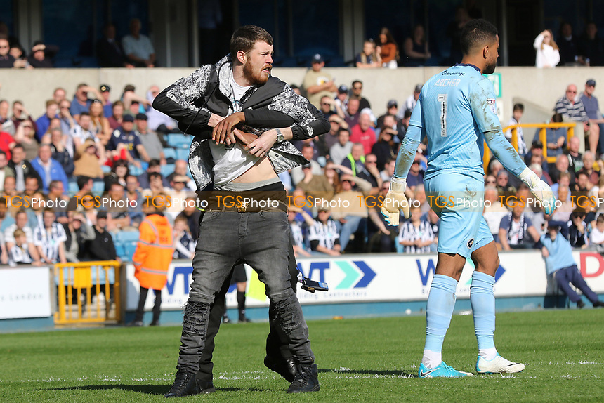 A Millwall steward grabs a pitch invader from behind during Millwall vs Oxford United, Sky Bet EFL League 1 Football at The Den on 22nd April 2017