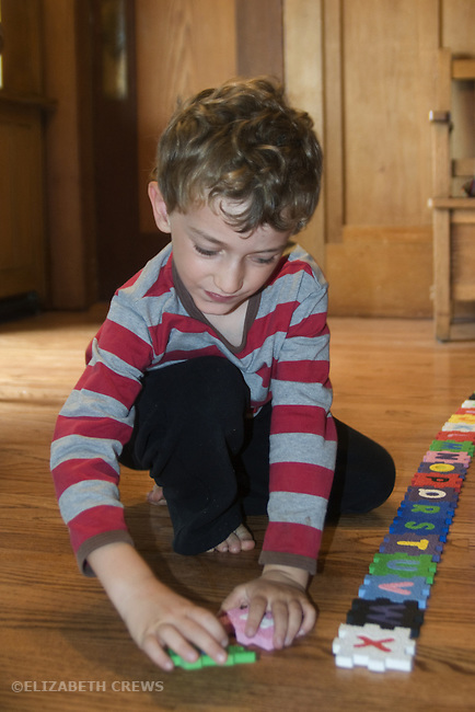 Berkeley CA Boy, five, laying out alphabet blocks in correct order  MR