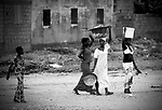 Senegalese women coming back from wash the clothes and pick up water.