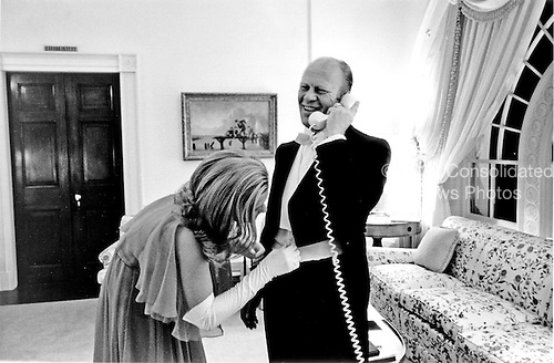 Susan Ford, daughter of United States President Gerald R. Ford and first lady Betty Ford, adjusts her Dad's cumberbun prior to a diplomatic reception at the White House in Washington, D.C. on October 5, 1974.  The President is speaking by phone to Mrs. Ford who is a the Bethesda National Naval Medical Center recovering from cancer surgery.  Susan is standing in for Mrs. Ford in her absence.<br /> Mandatory Credit: David Hume Kennerly / White House via CNP