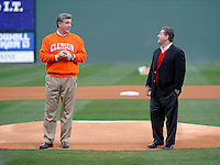 Athletics director Dan Radakovich, left, of the Clemson Tigers with athletics director Ray Tanner of the South Carolina Gamecocks prepare to throw out the first pitches on Saturday, March 2, 2013, at Fluor Field at the West End in Greenville, South Carolina. Clemson won the Reedy River Rivalry game 6-3. (Tom Priddy/Four Seam Images)