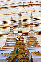 Myanmar, Burma.  Shwedagon Pagoda, Yangon, Rangoon.  Small Pagodas in foreground, base of main pagoda behind.