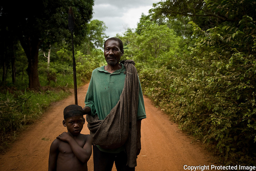 """Enosa Mawa, a congolese refugee on the road between Naandi and Nzara, South Sudan. He fled LRA attacks in Congo and now travels with a spear to protect his family. In the area round yambio villagers have organized """"arrow boys"""" a  sort of community watch to guard against  possible LRA attacks.."""