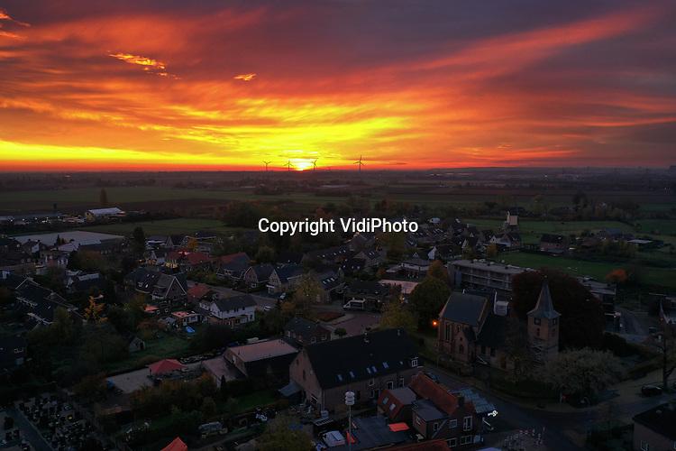 Foto: VidiPhoto<br /> <br /> VALBURG – Morgenrood, regen in de sloot. Zo luidt een oud Nederlands gezegde. Natuurliefhebbers en fotografen in Gelderland konden hun geluk niet op donderdagmorgen. Vroege vogels zagen een uitzonderlijk mooie zonsopkomst, dankzij laaghangende bewolking waartegen de zon reflecteerde. Deze reflectie zorgde voor een extra rode gloed op het landschap of in de dorpen, zoals hier Valburg in de Betuwe. Zo'n indrukwekkende zonsopkomst komt maar enkele keren per jaar voor. De eeuwenoude wijsheid bleek overigens ook ditmaal weer te kloppen.