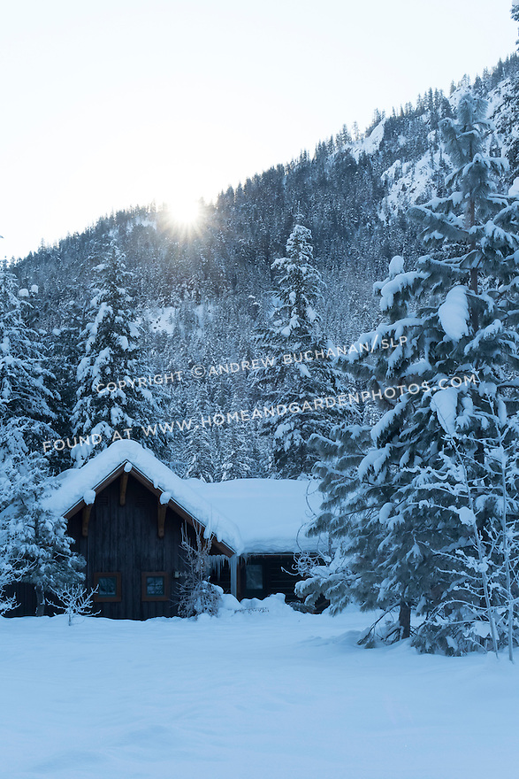 A cabin sits tucked at the base of a hillside amid snow-covered pine trees in this beautiful winter scene.