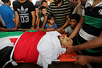 Palestinian relatives mourn over the body of Ziad al-Barim, 25, who was shot dead by Israeli troops during clashes at Israel-Gaza border, during his funeral in Khan Younis in the southern Gaza strip on June 9, 2018. Four Palestinians were killed by Israeli fire on the Gaza border on June 8, the territory's health ministry said giving a new toll, as weeks of deadly clashes with protesters continued. Photo by Ashraf Amra