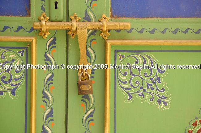 A decorative door and a gold door handle and lock in Marrakesh, Morocco.