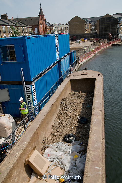 A barge delivers materials to a Genesis Housing Group construction site by the Grand Union Canal, close to the Harrow Road in North Paddington, London.
