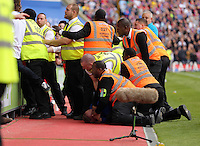 Pictured: A Swansea supporter is pinned to the ground by security stewards<br />