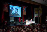 """Rosa Luxemburg-Konferenz 2016 am Samstag den 9. Januar 2016.<br /> Ueber 2500 Menschen sollen nach Angaben des Veranstalters, der Tagenszeitung """"junge Welt"""", zur 21 Rosa Luxemburg-Konferenz gekommen sein. Linke Verlage und Organisationen praesentierten sich den Konferenzbesuchern.<br /> Im Bild: Ein Live-Interview mit Alexej Markov, Gruender und Kommandeur der politischen Abteilung der kommunistischen Brigade """"Prisrak"""" in der Ostukraine. Er gruesst die Konferenzteilnehmer mit erhobener Faust.<br /> 9.1.2016, Berlin<br /> Copyright: Christian-Ditsch.de<br /> [Inhaltsveraendernde Manipulation des Fotos nur nach ausdruecklicher Genehmigung des Fotografen. Vereinbarungen ueber Abtretung von Persoenlichkeitsrechten/Model Release der abgebildeten Person/Personen liegen nicht vor. NO MODEL RELEASE! Nur fuer Redaktionelle Zwecke. Don't publish without copyright Christian-Ditsch.de, Veroeffentlichung nur mit Fotografennennung, sowie gegen Honorar, MwSt. und Beleg. Konto: I N G - D i B a, IBAN DE58500105175400192269, BIC INGDDEFFXXX, Kontakt: post@christian-ditsch.de<br /> Bei der Bearbeitung der Dateiinformationen darf die Urheberkennzeichnung in den EXIF- und  IPTC-Daten nicht entfernt werden, diese sind in digitalen Medien nach §95c UrhG rechtlich geschuetzt. Der Urhebervermerk wird gemaess §13 UrhG verlangt.]"""