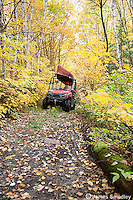 Hunter driving his ATV through a forest path in fall. ATVs riding off trail