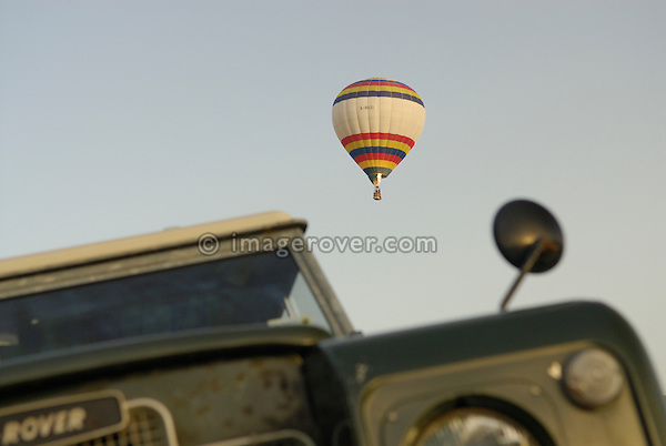A hot air balloon flying over a Series 3 Land Rover at the Dunsfold Collection of Land Rovers 2006 open day, Dunsfold, Surrey, England, UK.  --- No releases available. Automotive trademarks are the property of the trademark holder, authorization may be needed for some uses.