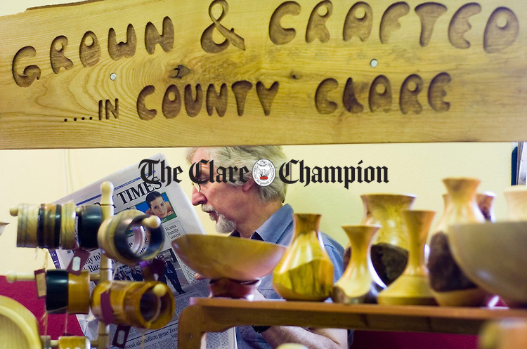 Woodturner William Edwatrds takes a break with his newspaper during the  Burren Craft Fair in Ballyvaughan. Photograph by John Kelly.