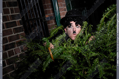 Charlie Chaplin mime Private detective hiding behind a bush spying on someone with scared surprised expression. Artistic humorous concept. Performing artist Peter Jarvis.