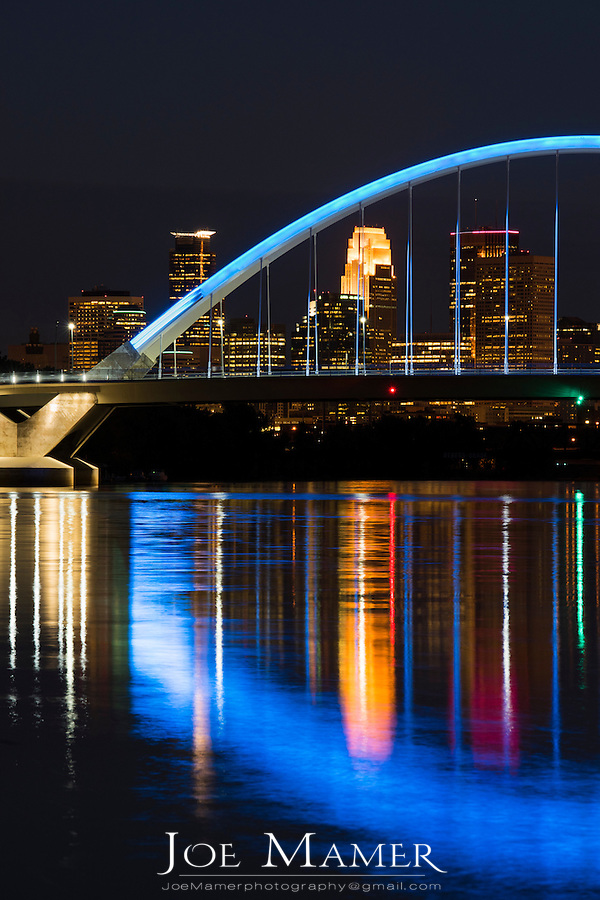 Lowery Avenue bridge with blue lighting over the Mississippi River and Minneapolis skyline at night.
