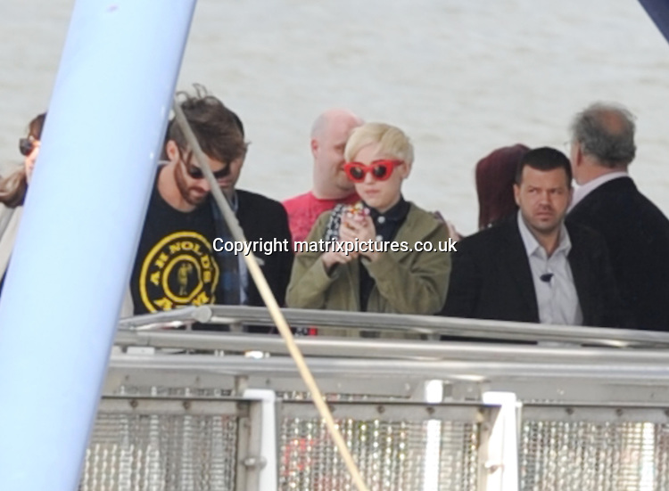 NON EXCLUSIVE PICTURE: MATRIXPICTURES.CO.UK<br /> PLEASE CREDIT ALL USES<br /> <br /> WORLD RIGHTS<br /> <br /> American actress and singer Miley Cyrus is seen using her phone as she arrives by boat at the O2 Arena in South-East London.<br /> <br /> MAY 6th 2014<br /> <br /> REF: LTN 142176