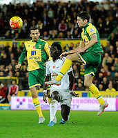 Robbie Brady of Norwich City and Bafetimbi Gomis of Swansea City run into each other during the Barclays Premier League match between Norwich City and Swansea City played at Carrow Road, Norwich on November 7th 2015