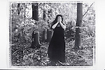 woman covering face and standing in woods
